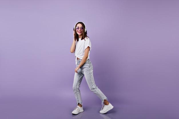 ヘッドフォンで音楽を聴いているジーンズのスリムな女の子のフルレングスのショット。踊っている白いスニーカーの女性モデルの肖像画。