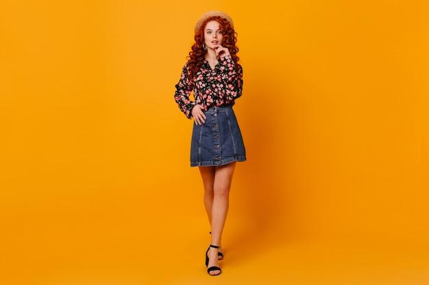 オレンジ色のスタジオでスタイリッシュなデニムスカート、フラワーピックと帽子のシャツでスリムな若い女性のフルレングスのショット。
