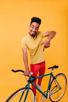 楽しんでいる赤いズボンで笑顔の黒人男性のフルレングスのショット。自転車でアクティブなアフリカ人の屋内の肖像画。