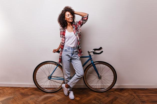 자전거와 함께 화려한 곱슬 아가씨의 전체 길이 샷. 포즈를 취하는 동안 그녀의 머리를 만지고 낙관적 인 흑인 소녀.