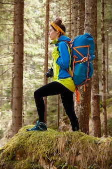 Снимок в полный рост спортивной туристки в хорошей физической форме, стоящей на холме на фоне деревьев в лесу