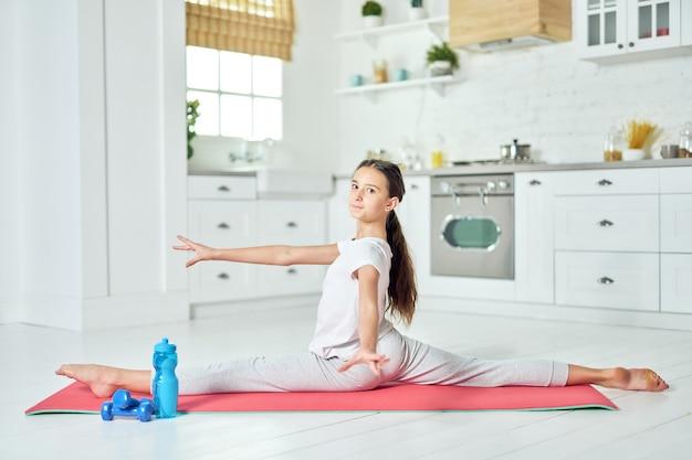 운동복을 입은 스포티한 히스패닉 10대 소녀의 전체 길이 사진은 카메라를 보며 웃고 집에서 매트에서 운동하는 동안 분할을 합니다. 운동, 건강한 라이프 스타일 개념입니다. 측면보기