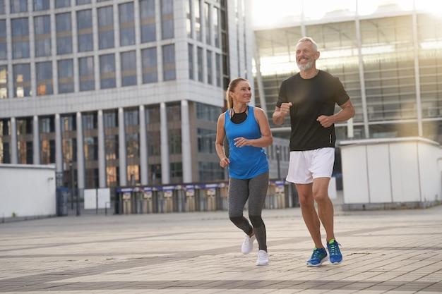 スポーツウェアで一緒にジョギングしているスポーティな中年カップルの男性と女性のフルレングスショット