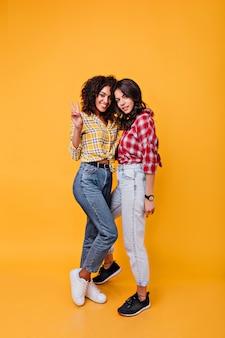 Снимок в полный рост стильных подруг в джинсах мамы. девушки с темными вьющимися волосами в позе хорошего настроения.