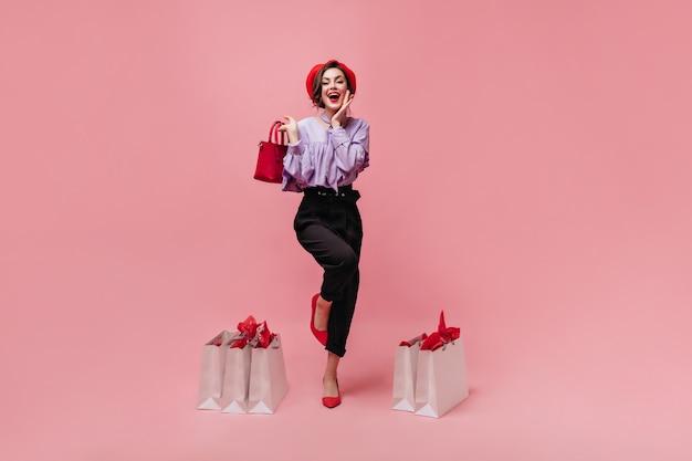 Снимок в полный рост стильной женщины, одетой в брюки, блузку, берет и туфли на высоких каблуках. девушка держит красную сумку и позирует с пакетами на розовом фоне.