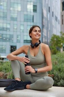 Снимок в полный рост уставшей, но довольной девушки после кардиотренировок пьет пресную воду держит бутылку с удовольствием смотрит в сторону, носит спортивную одежду, кроссовки сидит расслабленно, современные строители стремятся быть здоровее