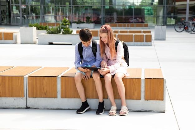 학교 근처에서 디지털 태블릿을 사용하고 숙제를 하는 두 명의 어린 10대 형제의 전체 길이 사진, 현대 교육에서 기술 사용 개념