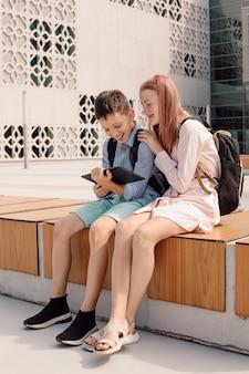 숙제를 하는 학교 근처에서 디지털 태블릿을 사용하는 두 명의 어린 십대 형제의 전체 길이 샷...