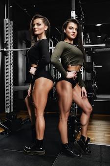 체육관에서 함께 서있는 운동복에 두 젊은 여성의 전체 길이 샷. 카메라를보고하는 헬스 클럽에있는 자매.