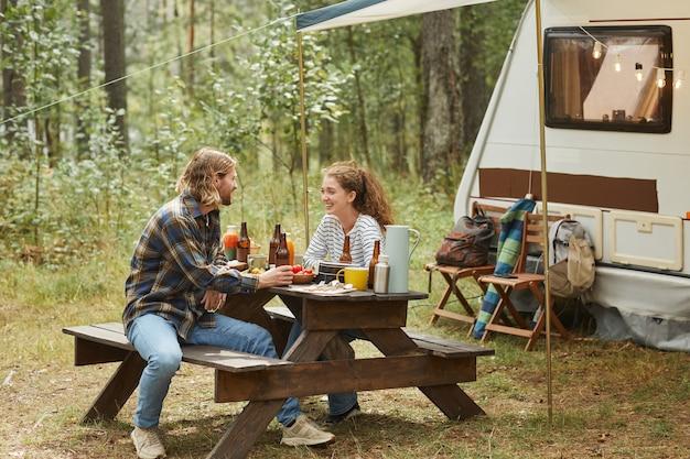トレーラーバンのコピースペースでキャンプしながら屋外でピクニックを楽しんでいる若いカップルの全身ショット