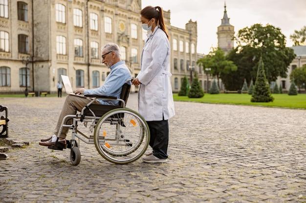 車椅子で回復中の高齢患者の世話をしている若い女性医師の全身ショット