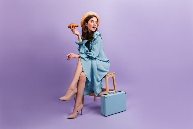 エレガントな青いドレスを着た若い女性のフルレングスのショット。女性はスーツケースの隣の椅子に座って、おいしいクロワッサンを持っています。
