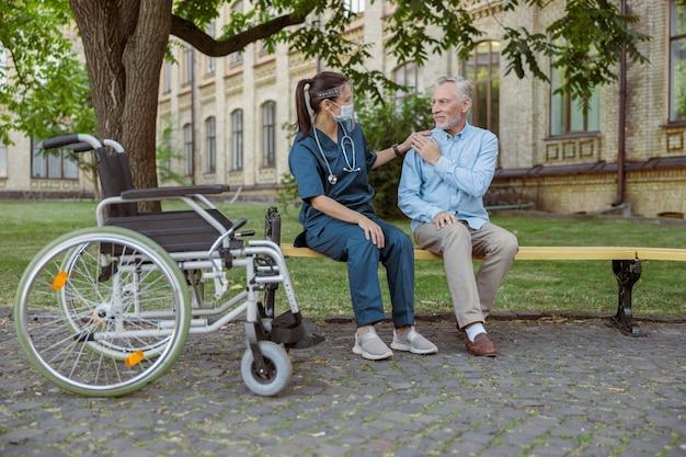 男性患者を回復する老人をサポートするフェイスシールドを身に着けている若い看護師の全身ショット