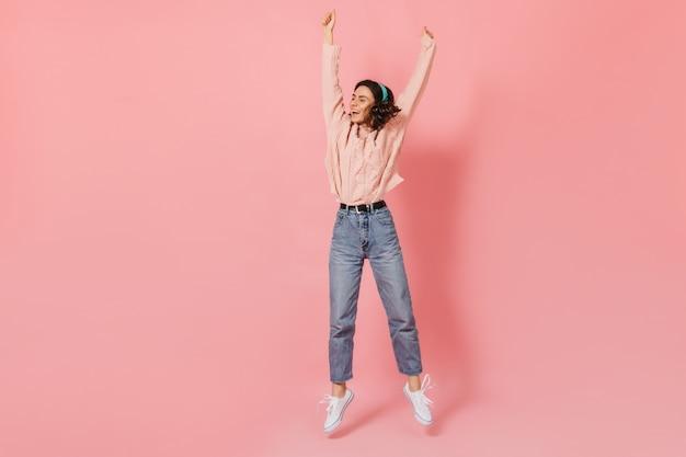 ピンクの背景に腕を上げてジャンプする若い女性のフルレングスのショット。ポーズをとって笑っているヘッドフォンの女性。