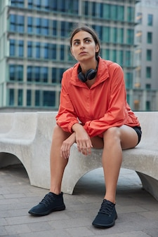 Full length shot of pensive european sportswoman takes break after cardio training dressed in activewear sits on stone against city
