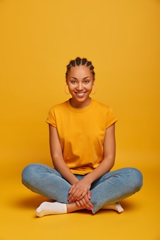 Colpo integrale di donna spensierata positiva siede gambe incrociate, sorride delicatamente, vestita casualmente, gode di atmosfera domestica, isolata sullo spazio vuoto muro giallo sopra persone, stile di vita