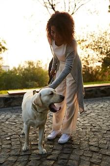 Colpo integrale della giovane signora abbastanza in buona salute che cammina di mattina nel parco con il cane