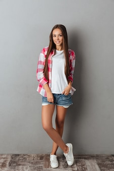 Full length shot of pretty smiling girl in checkered shirt