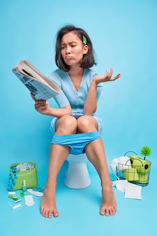 Full length shot of puzzled asian woma reads unpleasant news from newspaper sits on toilet bowl has panties pulled down on legs suffers from diarrhea on blue in restroom
