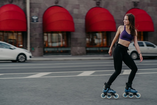Full length shot of slim active young woman rides rollerblades for strong muscles enjoys favorite hobby has good exercises for figure and health improves muscular endurance increases strength