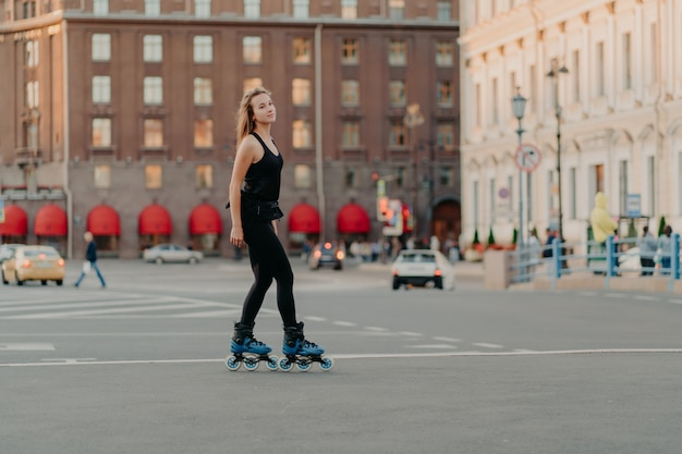 Full length shot of slim dark haired woman rollerblades on asphalt road dresed in black sportsclothes enjoys outdoor activities exercises for healthy and strong body. sport and hobby concept