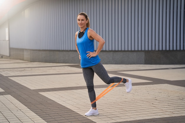 Full length shot of sporty woman in sportswear stretching her legs using resistance band while