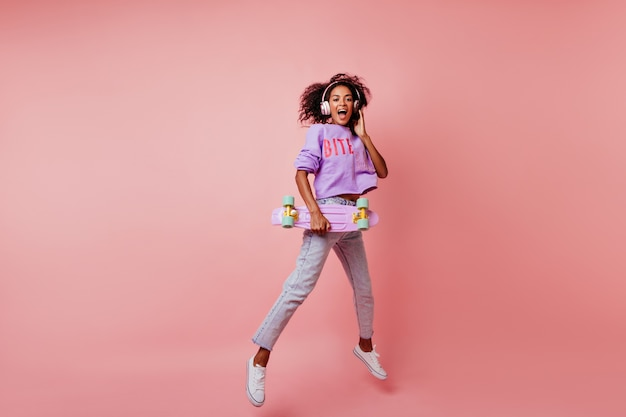 Full-length shot of stunning black woman in stylish jeans jumping on pink. curly african girl with skateboard expressing positive emotions.