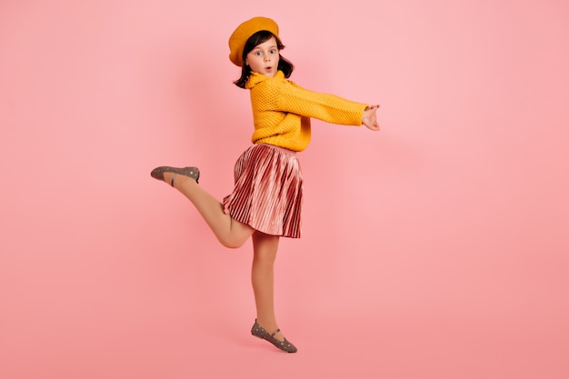 Full length shot of stunning kid standing on one leg. carefree child jumping on pink wall.