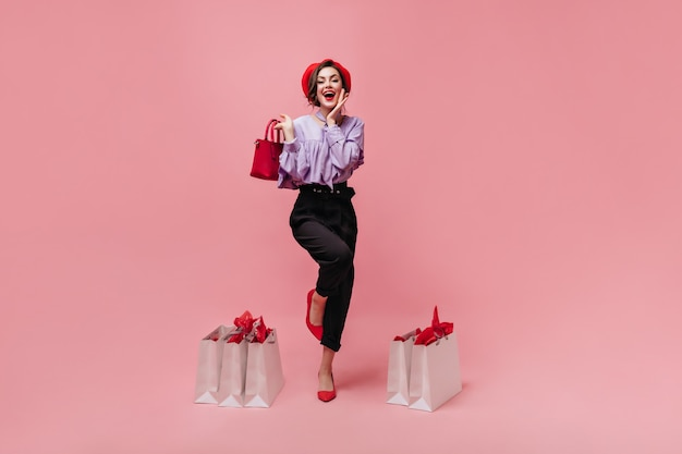 Full-length shot of stylish woman dressed in trousers, blouse, beret and high-heeled shoes. girl holding red bag and posing with packages on pink background.
