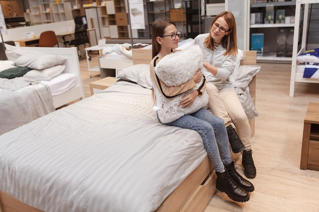 Full length shot of teenage girl and her mothersitting on a new bed at furniture store