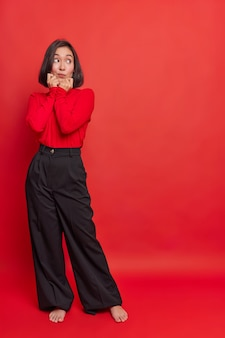 Full length shot of thoughtful asian woman with dark hair keeps hands on chin looks away at something interesting wears turtleneck black loose trousers stands bare feet indoor against red wall
