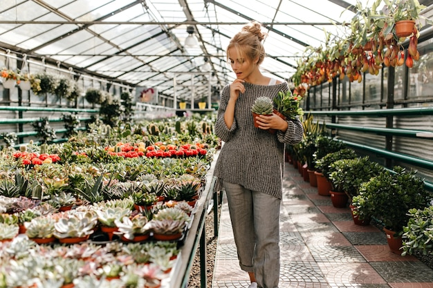 Full-length shot of thoughtful blonde woman in gray pants and sweater walking through greenhouse.
