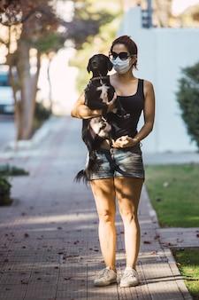 Scatto a figura intera di una donna con una maschera che tiene in mano un cucciolo carino