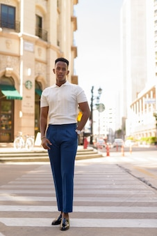 Full length shot of young african businessman outdoors walking over crosswalk