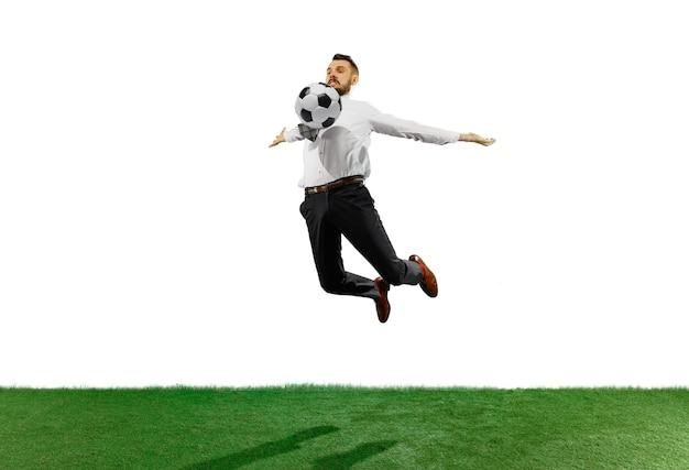Colpo integrale di un giovane uomo d'affari che gioca calcio isolato su priorità bassa bianca.