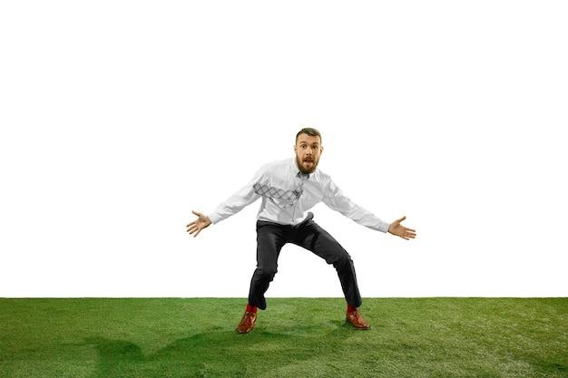 Colpo integrale di un giovane uomo d'affari che gioca a calcio isolato sul muro bianco
