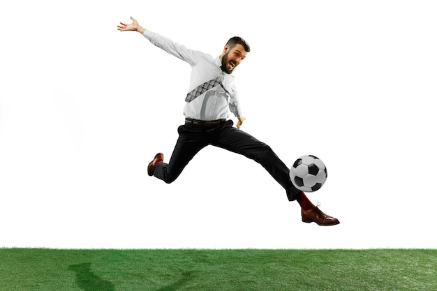 Full length shot of a young businessman playing football isolated on white wall