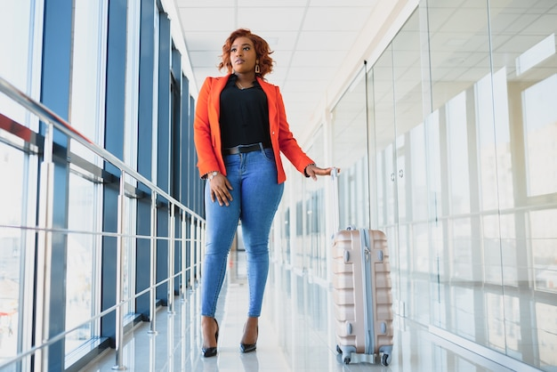 Full length side portrait of young black woman walking with suitcase in airport