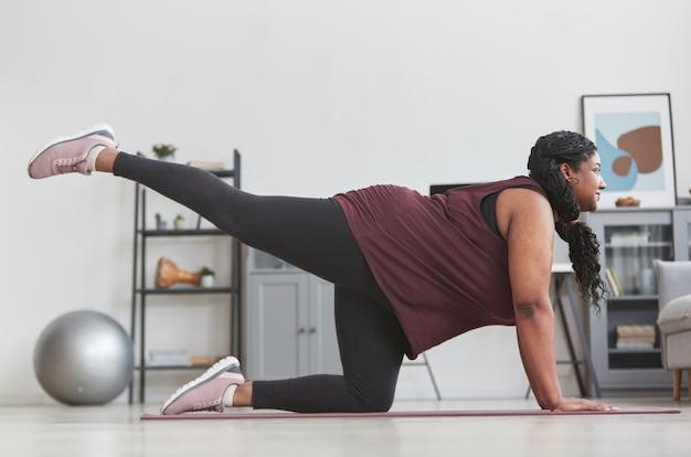 Вид сбоку в полный рост на фигуристую афроамериканку, тренирующуюся дома и улыбающуюся, растягиваясь на коврике для йоги, копия пространства
