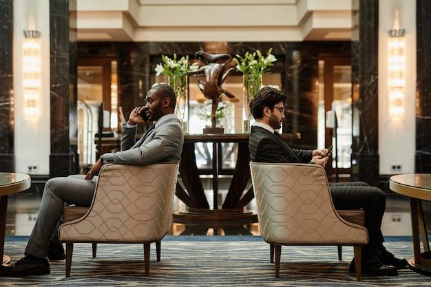 고급 호텔 로비의 안락의자에서 휴식을 취하는 두 명의 성공적인 사업가의 전체 길이 측면 전망