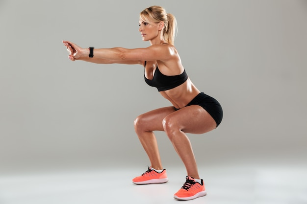 Full length side view of a athlete woman doing squats