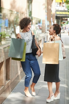 Full length side view of girlfriends laughing hard with shoppnig bags in the street