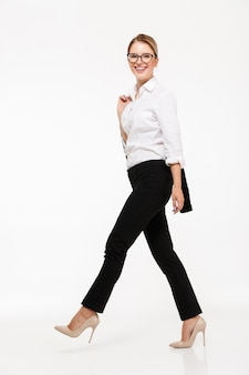 Full length side view image of smiling blonde business woman in eyeglasses walking in studio and  over white wall