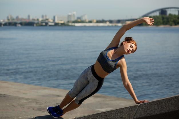 강에서 매력적인 운동 여성 측면 판자의 전체 길이 측면 보기