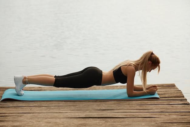 湖を背景に板を作る若い美しい女性の全身側面図