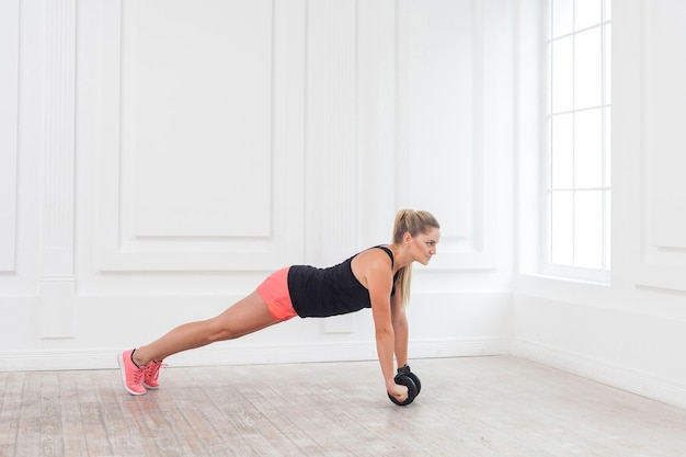 Full length side view portrait of athletic young woman in fit wear using dumbells in gym to workout and standing on perfect plank. indoor, studio shot, healthy lifestyle concept.