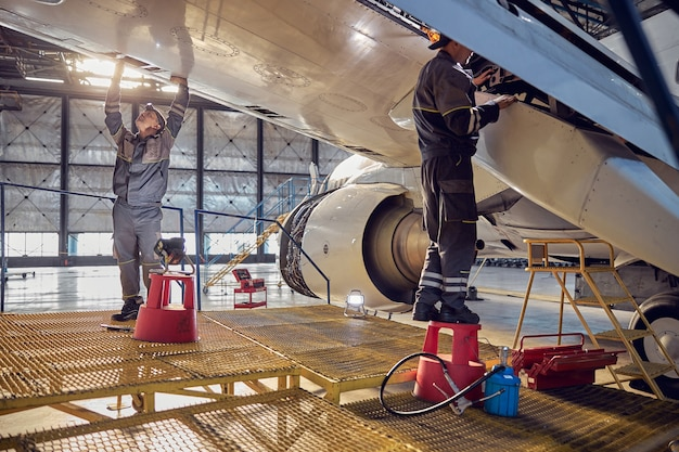 Full length side view portrait of men aviation mechanics fixing and checking spoiler and flaps on the airplane