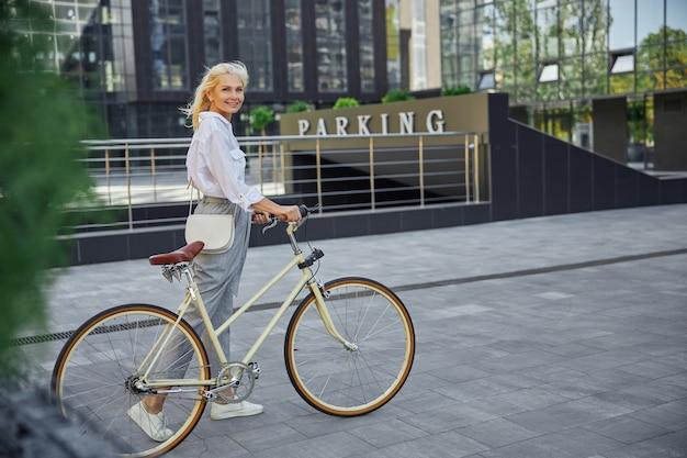빈 도심에서 복고풍 자전거를 탄 매력적인 금발 여성의 전체 길이 측면 보기 초상화
