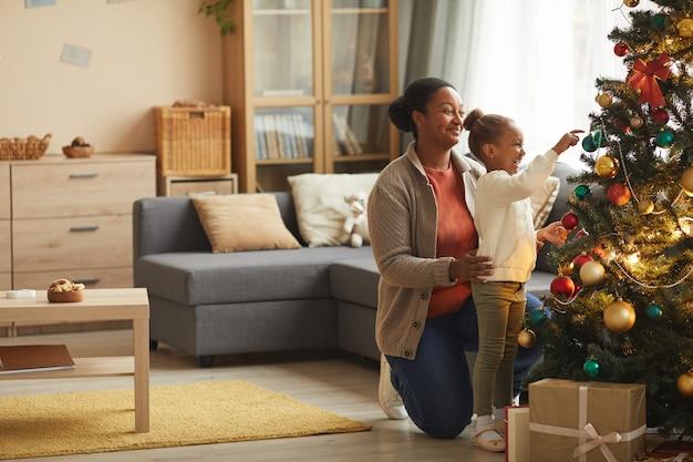 Портрет в полный рост симпатичной афро-американской девушки, украшающей елку с улыбающейся счастливой мамой в уютном домашнем интерьере, копией пространства
