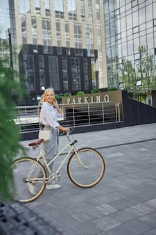 지하 주차장 앞에 현대적인 자전거가 서 있는 잘 생긴 여성의 전체 길이 측면 보기 초상화